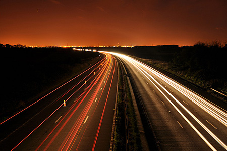 Car light trails on road through timelapse